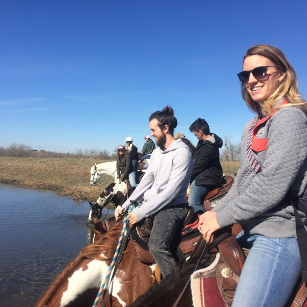 Group of horseback riders enjoying a stop at the pond at our Central Texas dude ranch, which is just twenty minutes away from the heart of San Marcos