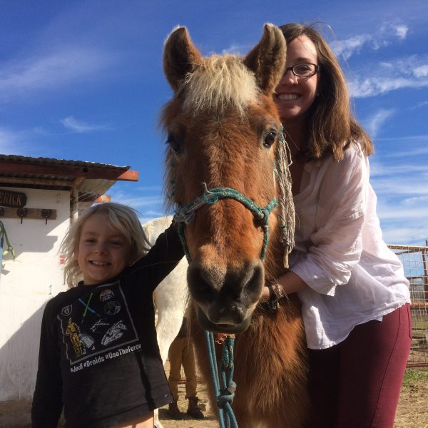 Blonde boy in long sleeve shirt stands next to his beloved blonde pony named Texas Glory, standing with horseback riding instructor Kathryn Hetzendorfer