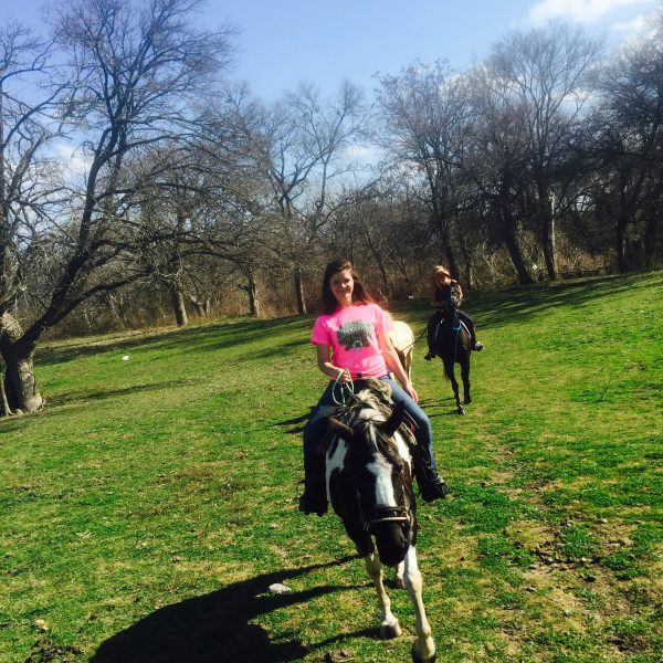 Forward shot by equine photographer who is mounted, but not pictured, of black and white paint horse with white blaze in green pastures in Hutto, riding with student in bright pink shirt and horse trainer bringing up the rear