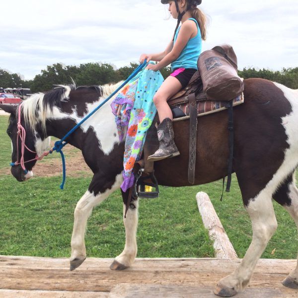 Black and white paint mare walks on horseback riding obstacle with youth play day rider, eaight years old, pictured in shorts and blue tank top