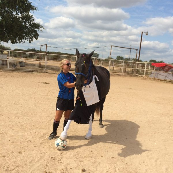 Texas horse trainer, MacCoy, stands with beloved mare, Black, who has her hoof planted firmly on a soccer ball after some summertime fun in Austin horseback riding stables