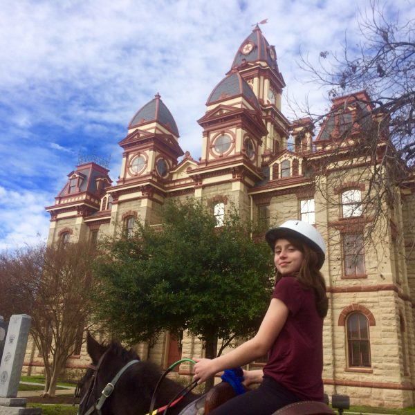 Traveler on horse vacation visits central Texas dude ranch and takes a ride to downtown Lockhart