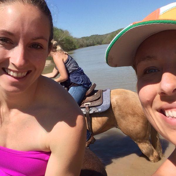 two women horseback riding in the colorado river