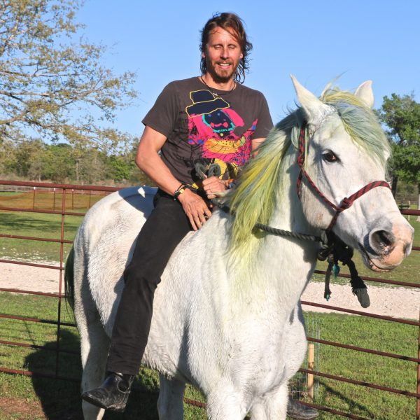 man rides percheron arabian bareback, horse is sporting a green adn blue mane as a leftover hair dye job from his stint as the official SXSW unicorn