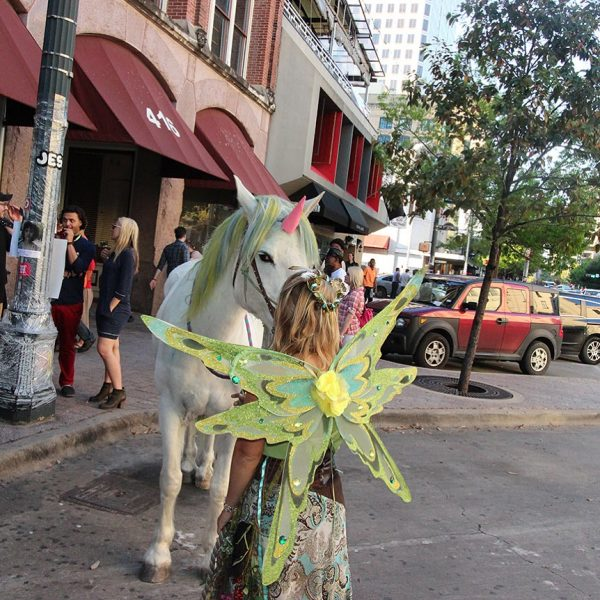 Austin fairy and SXSW unicorn pause for a quick kiss on the streets of downtown Austin