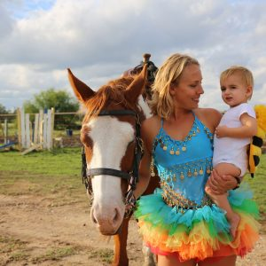 sorrel and white paint mare hangs her head quietly while equine trainer MacCoy gets silly with little baby dressed in halloween bumble bee outfit