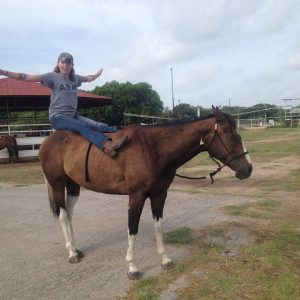 horseback riding student practices some yoga on registered paint mare during summer camp program at Round Rock horseback riding facility