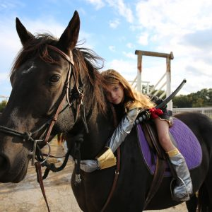 young horse lover poses with 15'3 hand black morgan horse cross, dressed as a knight, as a silly break away from the traditional hunter jumper lesson at Round Rock riding stables in Texas
