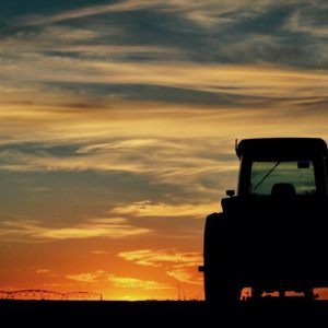 John deere tractor sitting off to the side, watching an amazing view of the sunset