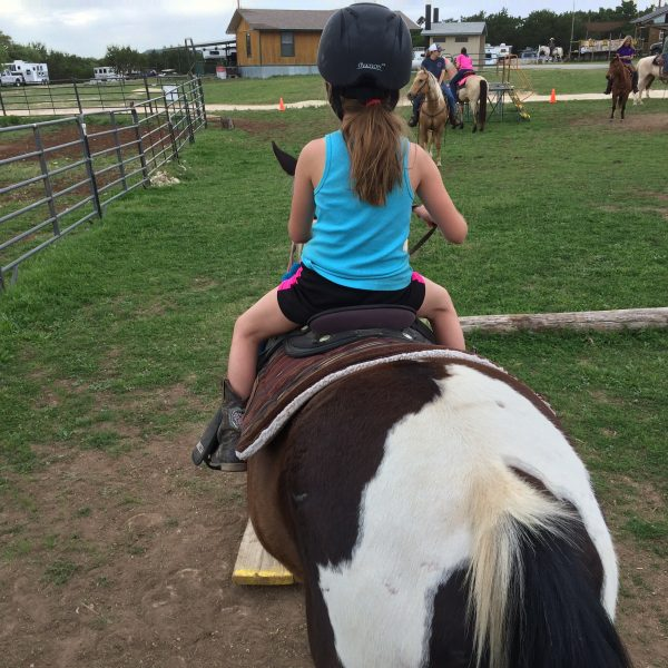 Young play day rider takes a gander at the horseback riding obstacles in the play day course in Killeen, she's wearing a light blue tank top and pictured from behind, getting ready to walk the plank while a group of horseback riding vacationers watches in the foreground