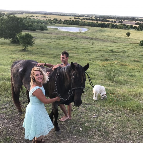 couple posing with one of our quarter horses, Moonshine.  Woman in blue floral dress smiling on the bluff top of our Texas dude ranch while her partner grins and prepares to mount up bareback.  White Akbash dog, Cecelia, stands by waiting for something fun to do in Austin